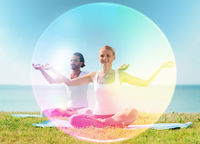 couple doing yoga in lotus pose with rainbow aura