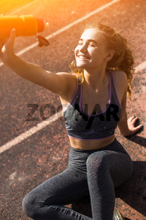 Young sportive girl with curly hairstyle on stadium