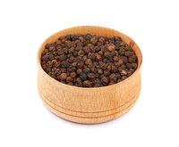 Wooden bowl full of black peppercorns
