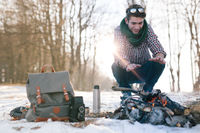 Handsome caucasian scout man warming his hands from bonfire in the winter in mountains.