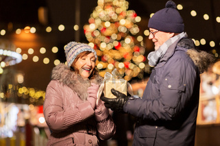 happy senior couple with gift at christmas market