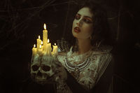 candles in skull, vampire, demonic woman dressed in white lace and silver jewelry. has fangs and thick brown hair