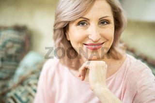 Beautiful mature woman gently smiles at camera