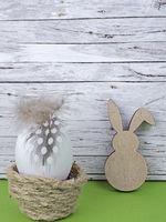 Ostern Hintergrund mit Osterei und Osterhase auf grün vor Holz