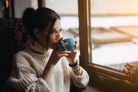 Girl enjoying flavor of coffee while relaxing at coffee shop