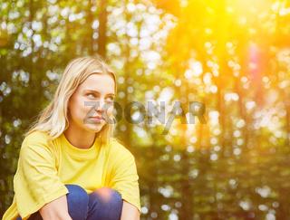 Junge Frau sitzt beim Nachdenken in der Natur