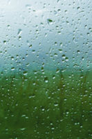 Natural background Drops on both sides of the glass from the rain and from the fogging abstract view, raindrops against the blue glass and the blurred landscape of the gradient of blue and green