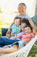 Chinese Grandparents In Hammock with Mixed Race Children
