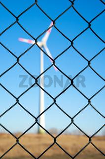 Windkraftanlage hinter einem Zaun