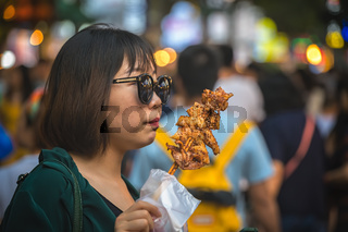 Chinese woman eating snack from a stick