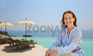 happy woman over infinity edge pool background