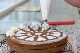 Konditor verziert Schokoladentorte mit Zuckermuster und Schlagobers - Nahaufnahme