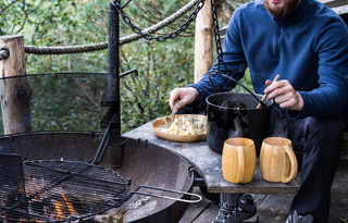 Frying pan and a pot on the fire, cooking pasta while camping