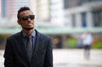 Young African businessman with sunglasses thinking in the city outdoors