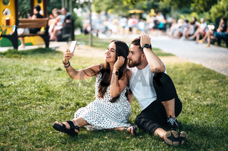 Handsome guy and pretty girl take a selfie in a park