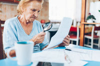 Elderly woman looking at her utility bills and paperwork