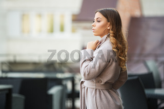 Young fashion woman in light grey coat walking in city street