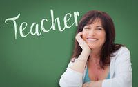 Teacher Written On Green Chalkboard Behind Smiling Middle Aged Woman
