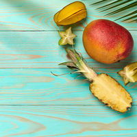 Corner frame of tropical fruits, mango, carambola and pineapple on a blue wooden background with copy space. Flat lay
