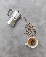 Italian coffee maker and fresh coffee beans coffee beans in the form of a drink stream on a gray stone background. Top view.