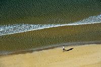 Einsamer Strandläufer läuft am Sandstrand von Praia da Luz