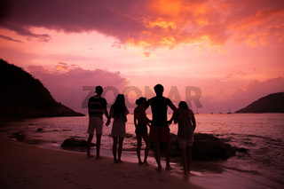Friends on beach at sunset