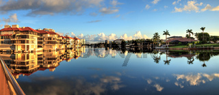 Reflection in the water of buildings along the Village at Venetian Bay