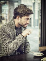 Attractive Man Drinking Coffee in a Bar