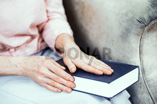 Female hands are laying on a blue book.