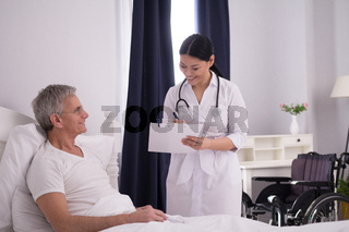 Nurse checking up on patient in bed.