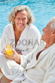 Senioren Paar sitzt entspannt am Pool