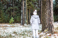 Woman winter wanderings in the pine forest dusted with snow