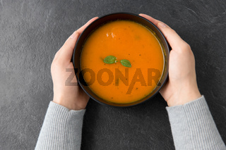hands with bowl of pumpkin cream soup on table