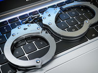 Handcuffs on the laptop keyboard. Internet cyber crime, hacking and online piracy concept.