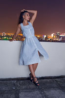 Outdoor portrait of young beautiful woman on rooftop with city view at night time
