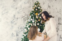 Woman with her daughter holding a box with a lot of Christmas silver decorations near to the Christmas tree