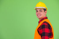 Profile view of happy young multi ethnic man construction worker looking at camera