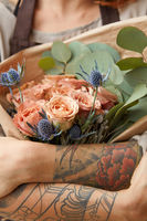 Close up of fresh tender roses and eryngium in a woman's hands with tattoo. Congratulation concept of Mother's Day.