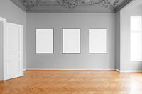 empty room with three blank picture frames hanging on wall in apartment -