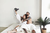 Couple posing in bed and taking selfie in morning