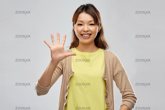 smiling asian woman showing five fingers