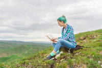 Portrait of a young hipster girl with multi-colored hair sitting on nature in the mountains reading a book. The concept of reading in nature. Education
