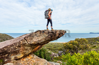 Hiker on rock cliff precipice with views