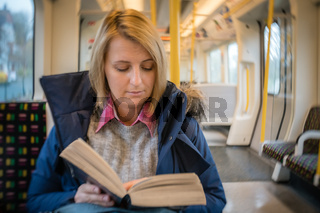 Woman reading book on a train