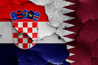 flags of Croatia and Qatar painted on cracked wall