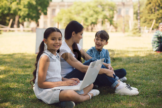 Teacher and two young students use laptop in park