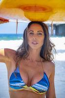 Lovely Brunette Bikini Model With Her Surfboard On A Beach