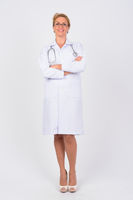 Full body shot of happy mature woman doctor smiling with arms crossed