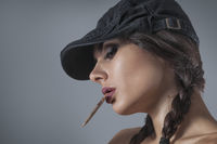 Dark portrait of young woman smoked hand-rolled cigarette
