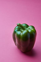 Fresh green paprika isolated on pink background